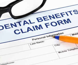 A dental benefits claim form with a pen and pair of glasses