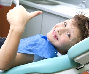 Boy gives thumbs up to Plano dentist after fluoride treatment