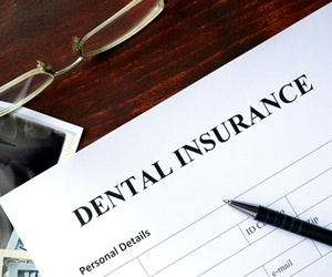 person filling out a dental insurance form to cover their emergency dental visit cost