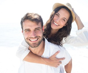 couple smiling on the beach after getting smile makeovers in Plano