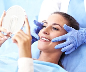 woman sitting in dental chair admiring her smile in handheld mirror