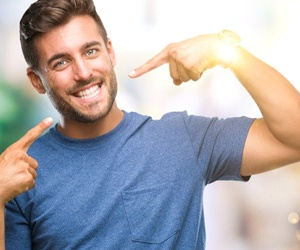 man pointing to his smile with straight white teeth